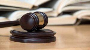 Anwaltshammer mit Gesetzbücher im Hintergrund